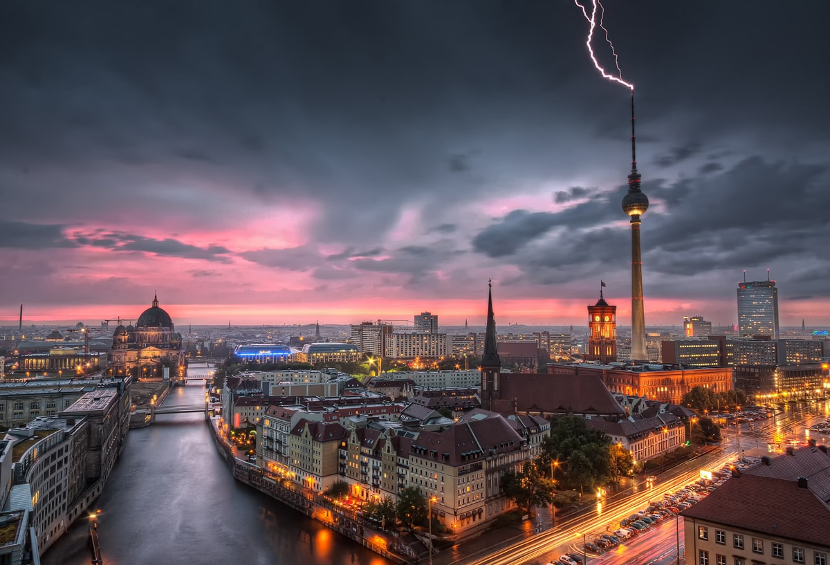 The lightning strikes the TV Television Tower on Alexanderplatz while the Berlin Skyline is pink enlightened