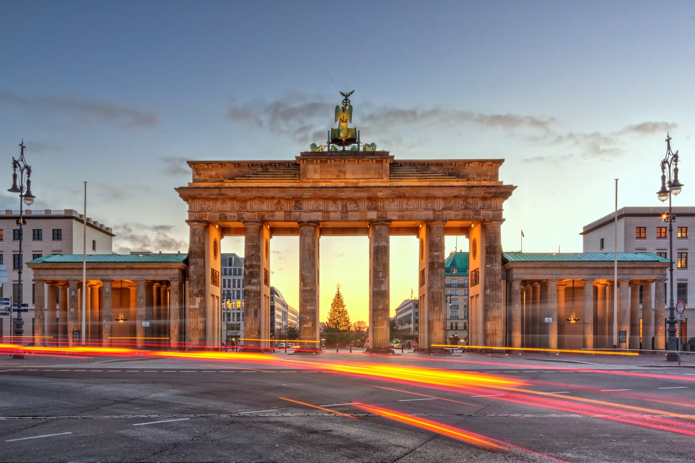 Brandenburg Gate in Berlin. HDR Photo from the West side of the illuminated sight at sunrise with light trails of the cars.