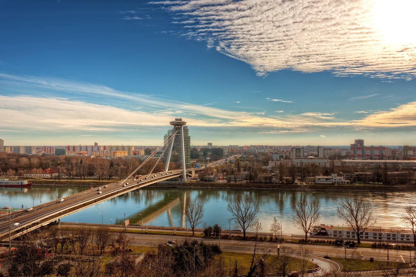 Skyline van Bratislava langs de Donau met de Nieuwe Brug en de UFO