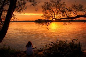 Meisje zit en staart naar de zonsondergang aan het Tegelmeer in het noorden van Berlijn