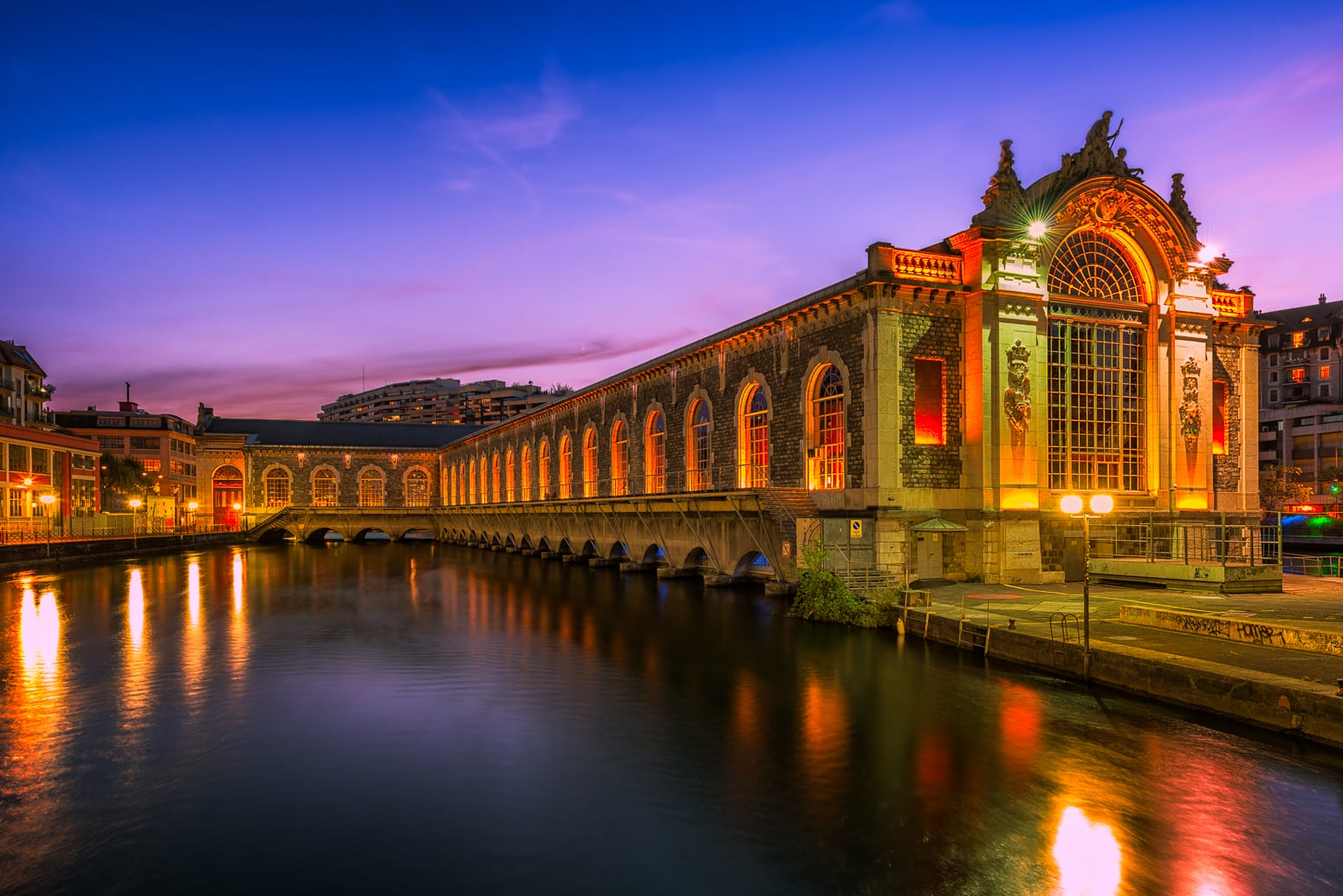 The Bâtiment des Forces Motrices BFM in Geneva, Switzerland in the midst of the river Rhône at night.