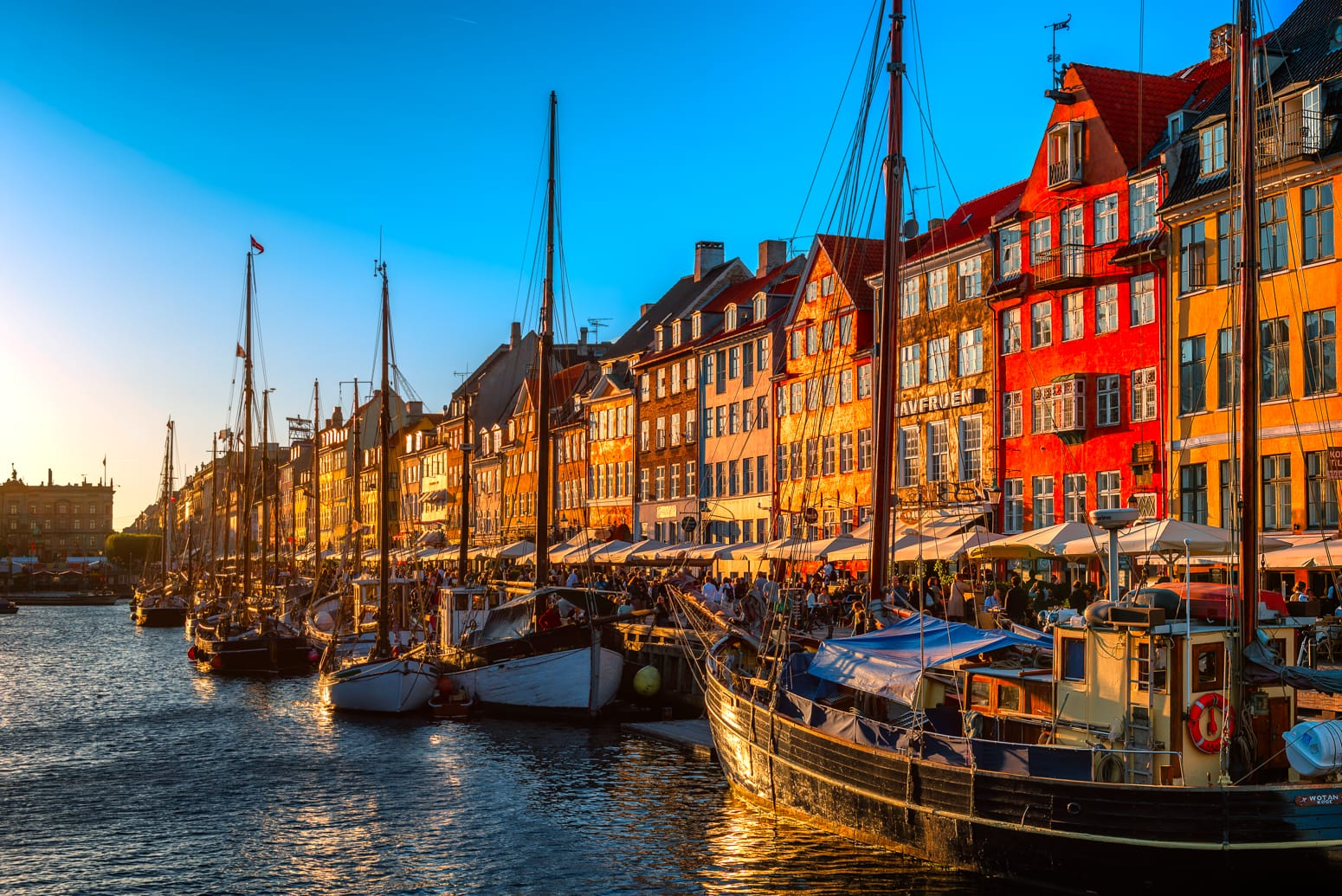 Nyhavn in Copenhagen, Denmark with colorful gabled houses at sunset.