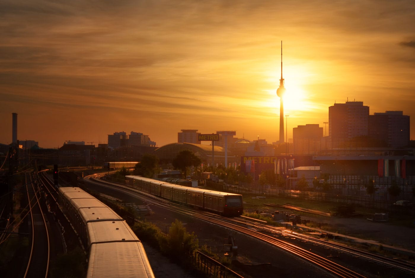S-Bahn metro trains in front of the Berlin Skyline at sunset