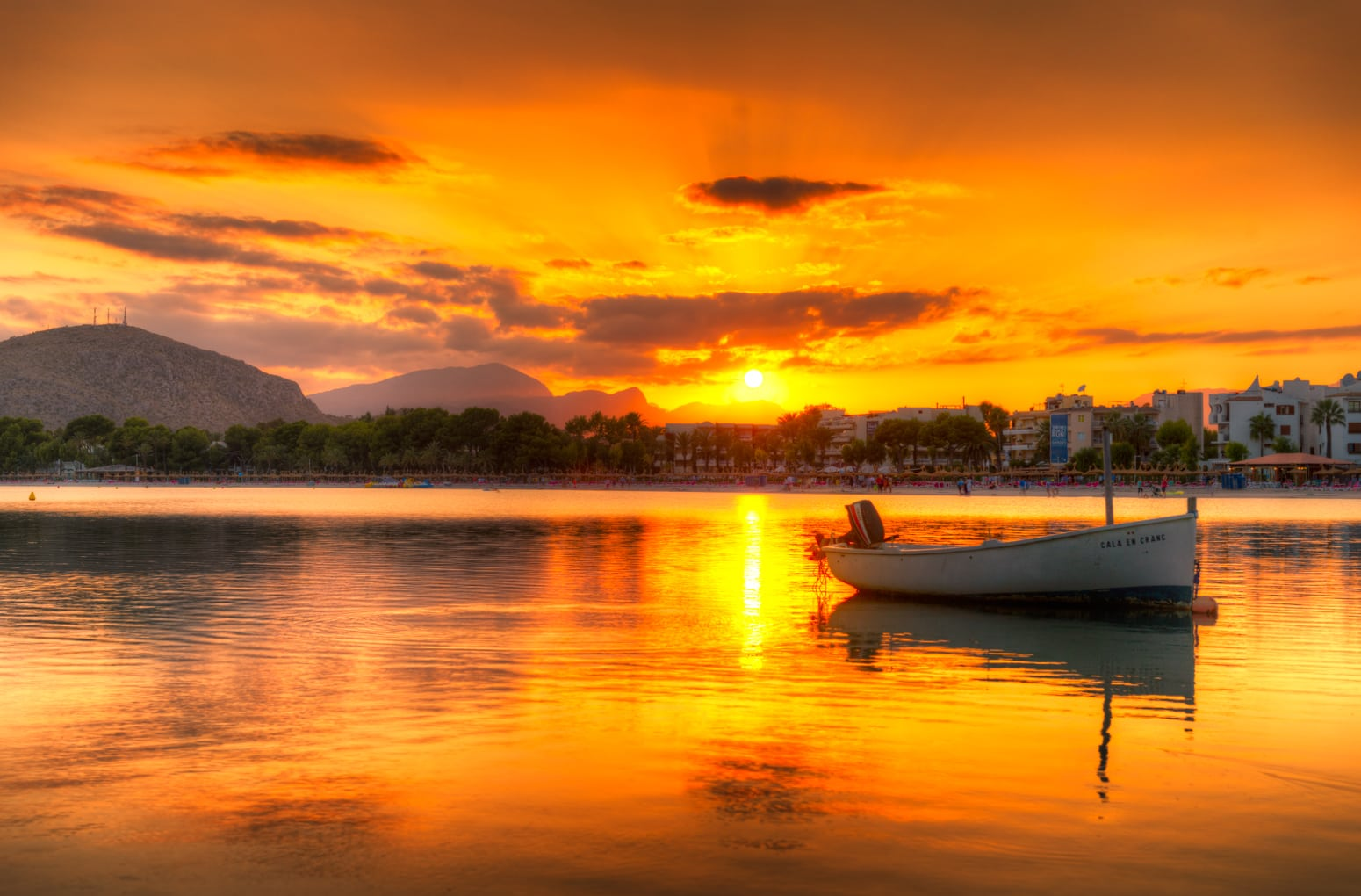The picture shows the bay of Port D'Alcudia while the light of the setting sun illuminates it. The town has a long history.