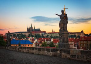 Statue auf der Karlsbrücke in Prag mit Prager Burg bei Sonnenaufgang