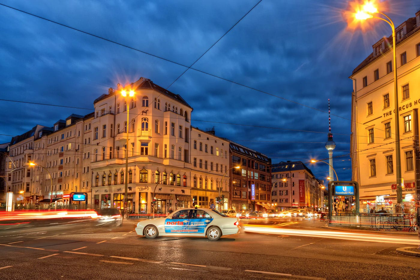 Rosenthaler Platz in Berlin with a taxi in the middle and the TV Tower in the background.