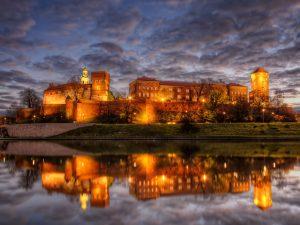 Die Wawel Burg in Krakau beleuchtet bei Nacht. HDR Foto aufgenommen kurz vor Sonnenaufgang von der anderen Seite der Weichsel.
