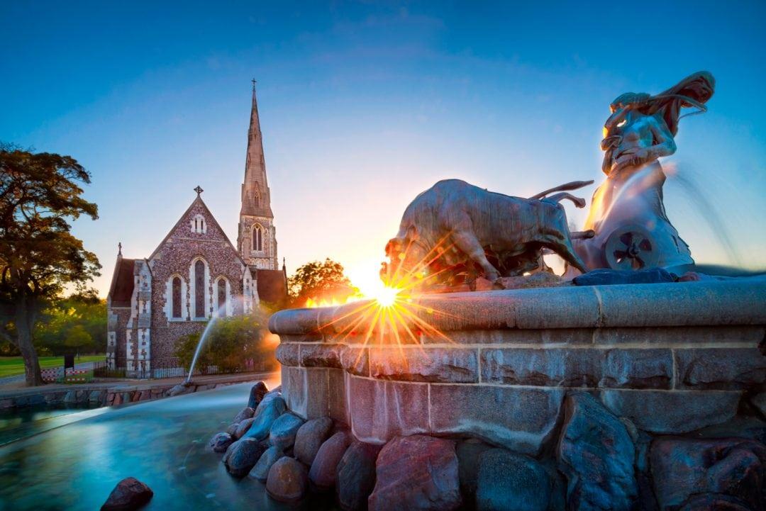 Gefion Fountain Copenhagen, Denmark in the setting sun. The fountain shows a woman and three bulls.