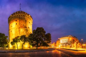 An evening photo of Thessaloniki White Tower and the National Theater of Northern Greece.