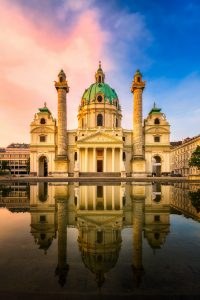 Karlskirche in Vienna during a sunrise with the pond in front
