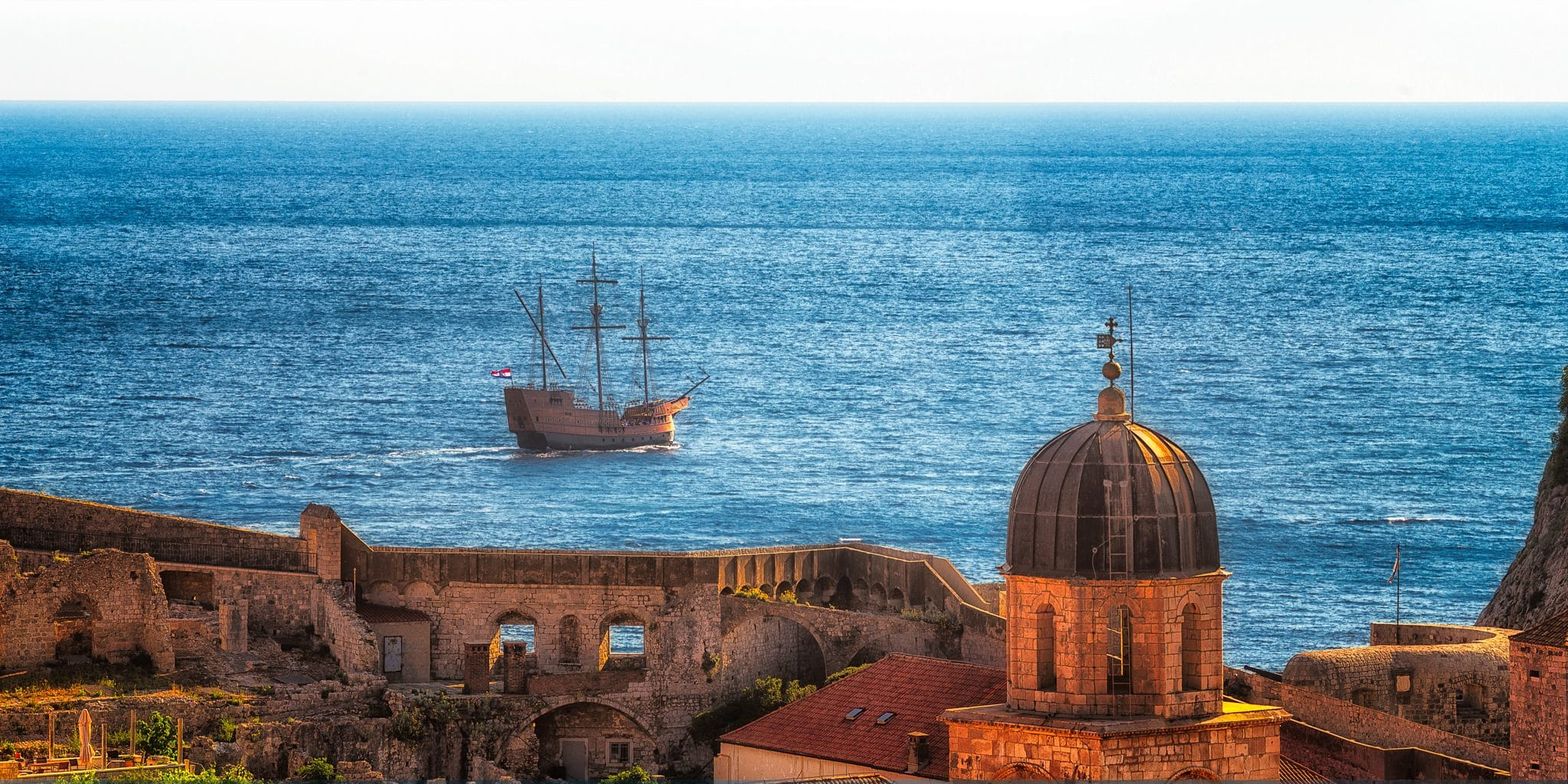 Dubrovnik in Croatia with an old-style boat passing it on the Mediterranean See. The view is from the walls of Dubrovnik.
