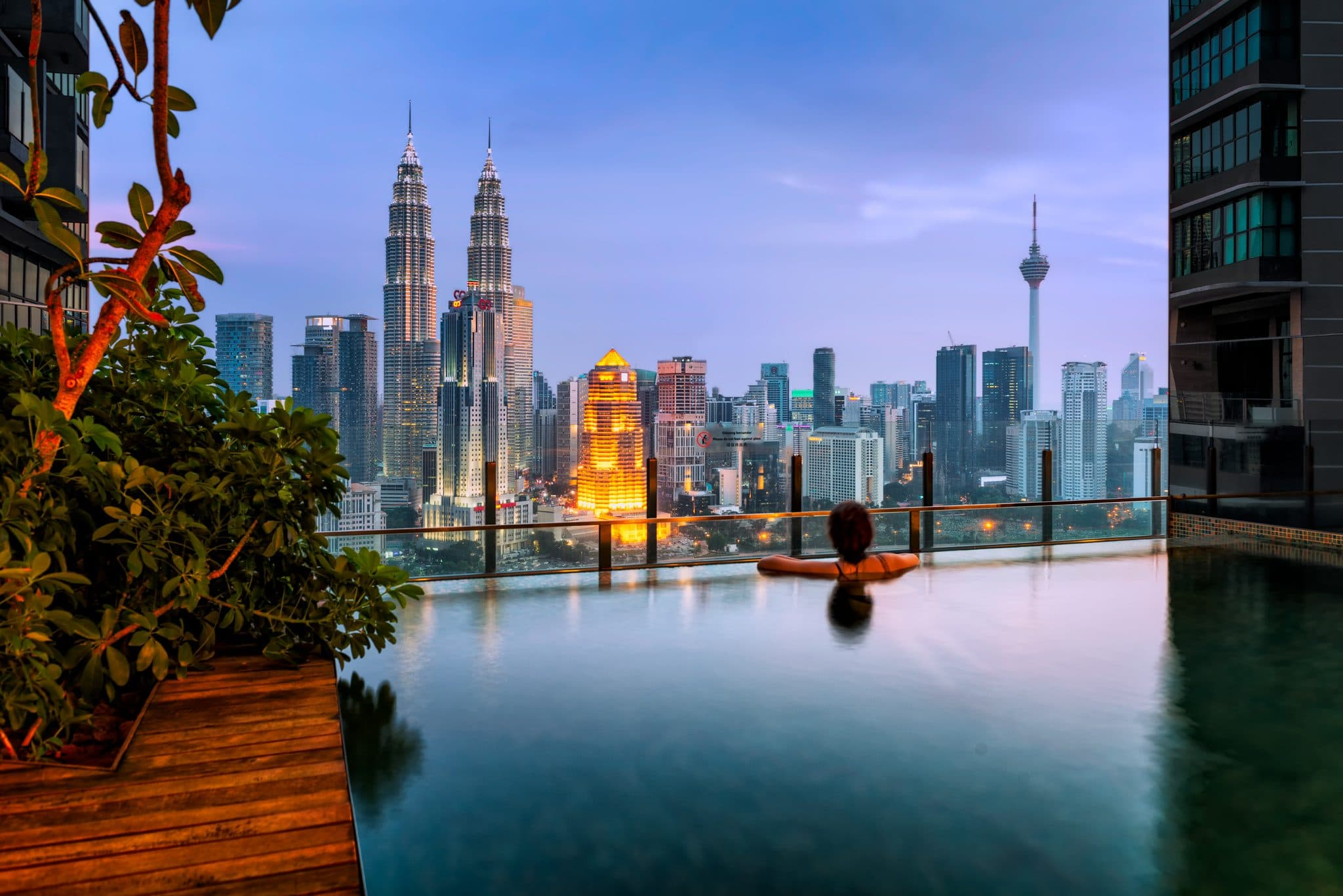 View over Kuala Lumpur city in Malaysia during a sunset from infinity pool.
