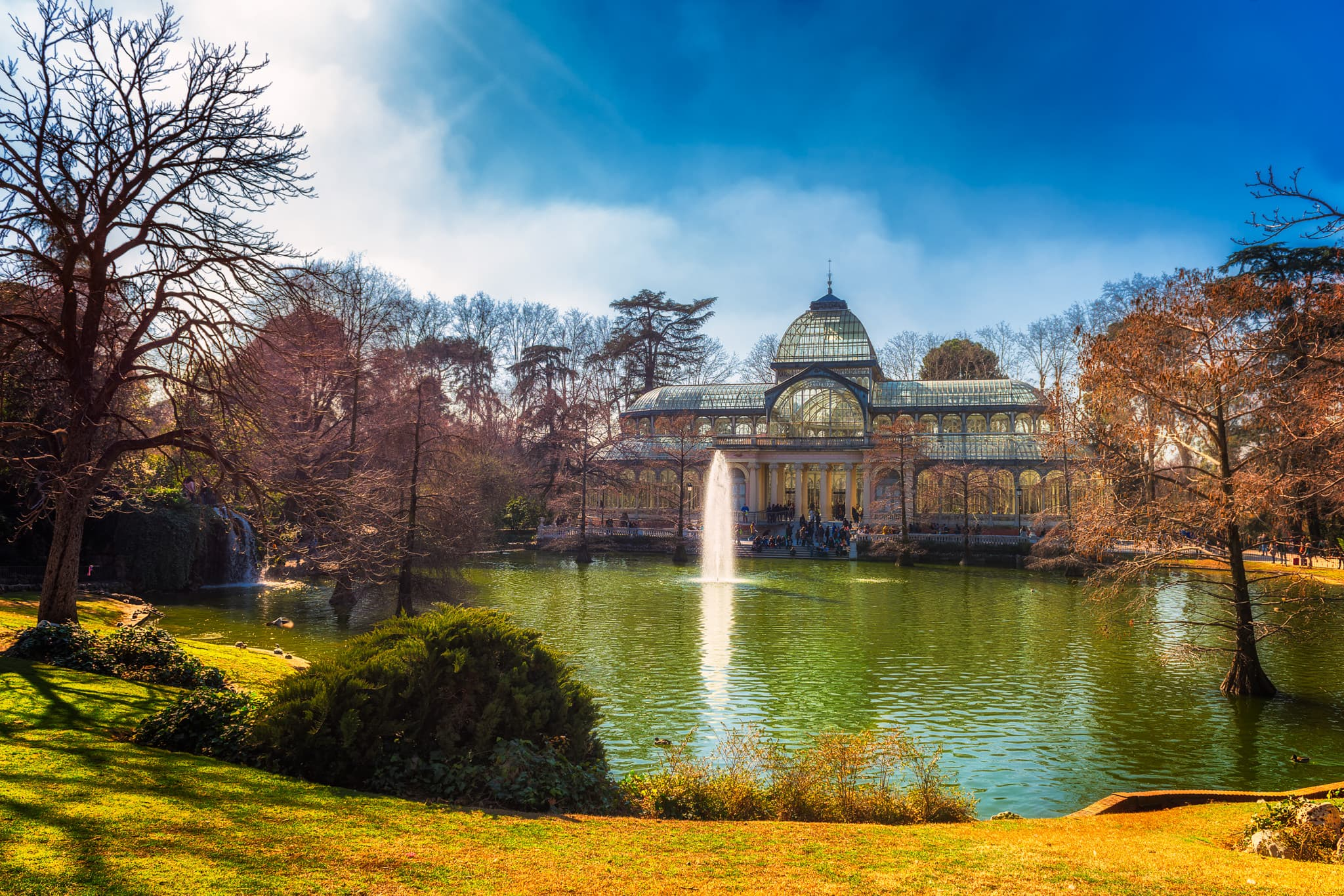Photograph of Crystal Palace in Buen Retiro Park in Madrid with the pond in foreground. Photo was taken during a sunny day in winter.