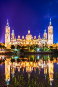 El Pilar Cathedral and its reflection in The Ebro River during the night in Zaragoza, Spain.