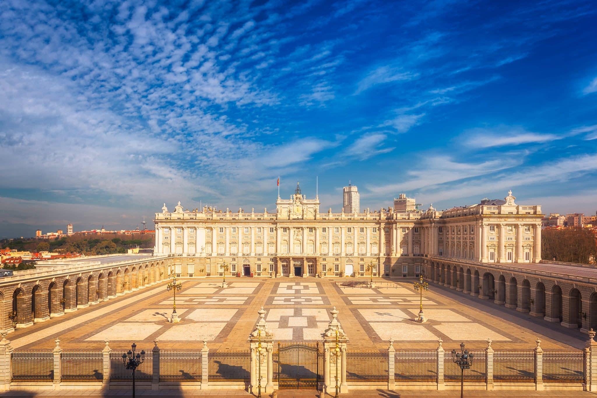 The Royal Palace of Madrid and The Plaza de la Armeria during a sunny day in the winter.
