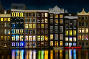 Night view of Amsterdam, Netherlands – View of the canal, boats and houses.
