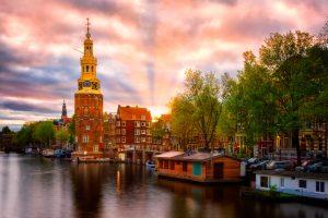 Amsterdam, Montelbaanstoren bij zonsondergang - uitzicht op de gracht, Nederland.