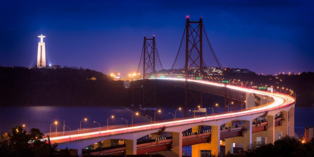 The 25 de Abril Bridge and Christ The King statue on Tagus River – Lisbon, Portugal.