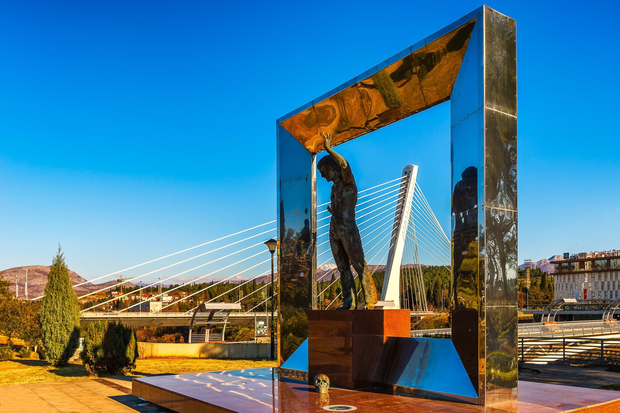 Vladimir Vysotsky-monument met de Millenniumbrug op de achtergrond in Podgorica, Montenegro.