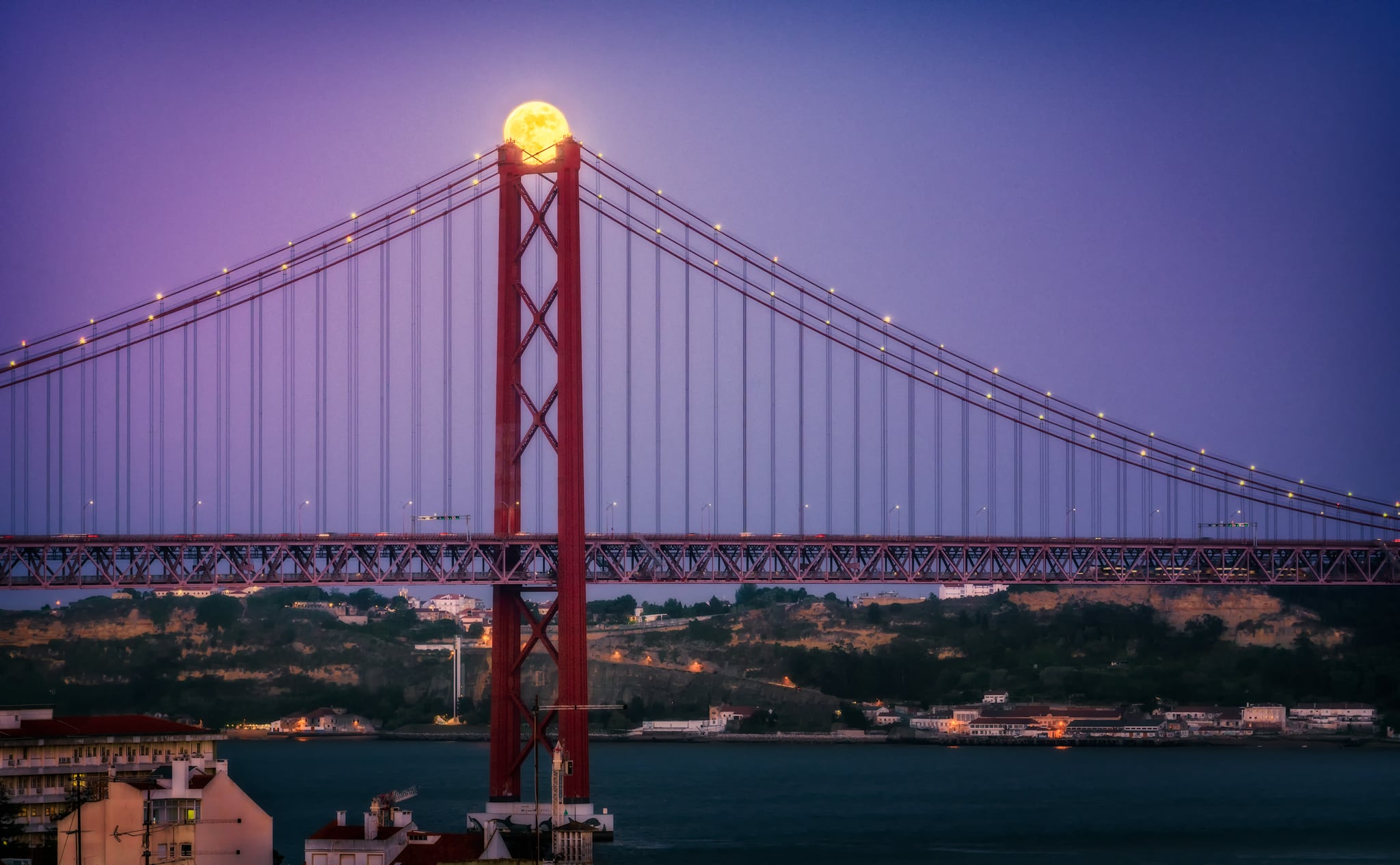"The rising fullmoon also called super moon over the 25 de Abril Bridge (""Ponte 25 de Abril"") in Lisbon, Portugal"
